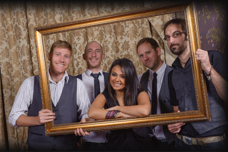 The Junos holding a picture frame at a wedding in Solihull